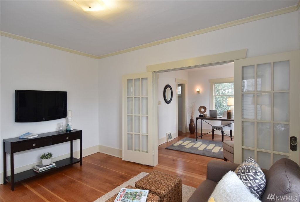 The back wall of a living area features French doors leading to a small office