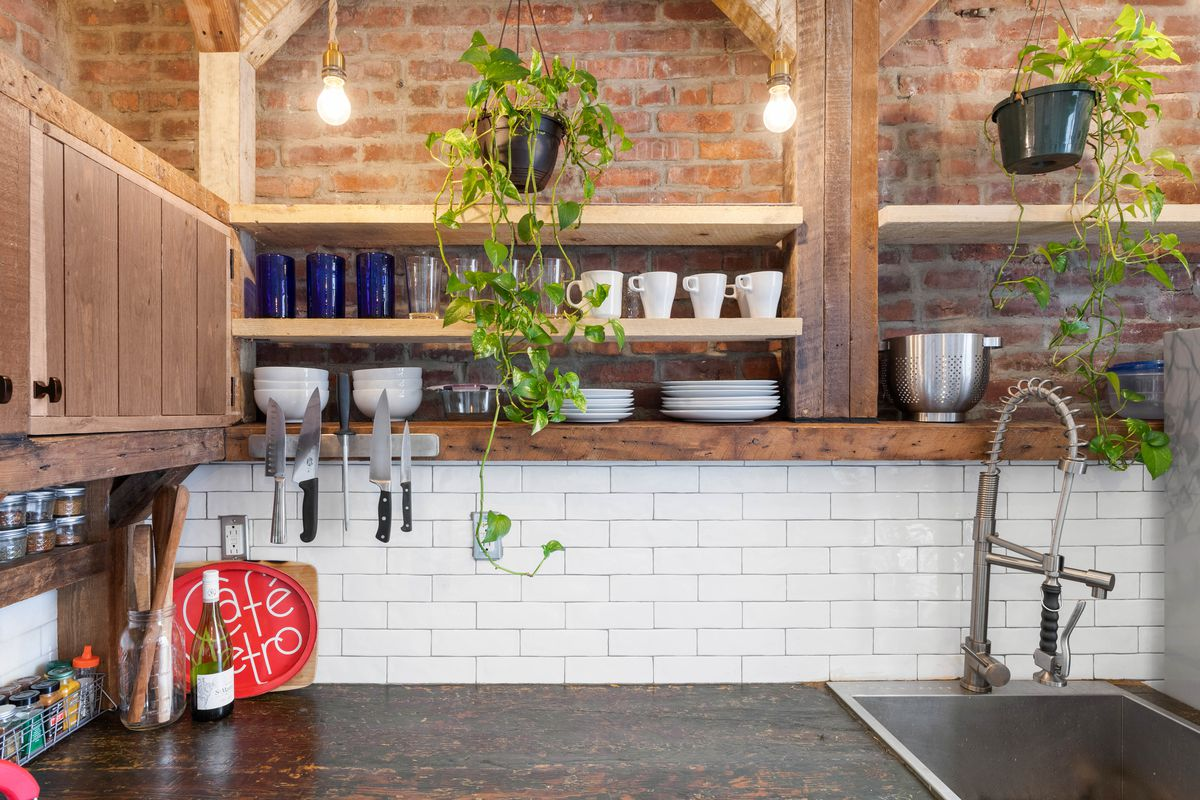 A kitchen with exposed brick and reclaimed wood.