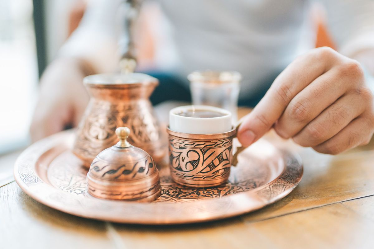 a tray of Turkish-coffee, served in elaborately-hammered copper posts and cups