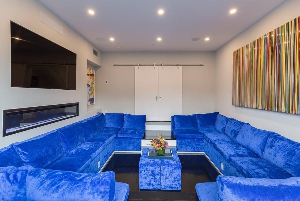 A sunken living room with a sectional couch dominating the space, and there's a TV mounted behind one side of the couch.