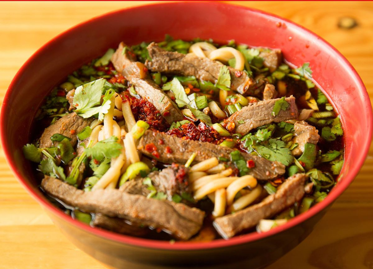 Noodles and beef floating in a spicy broth in a red bowl. The bowl is garnished with chile flake and cilantro leaves.