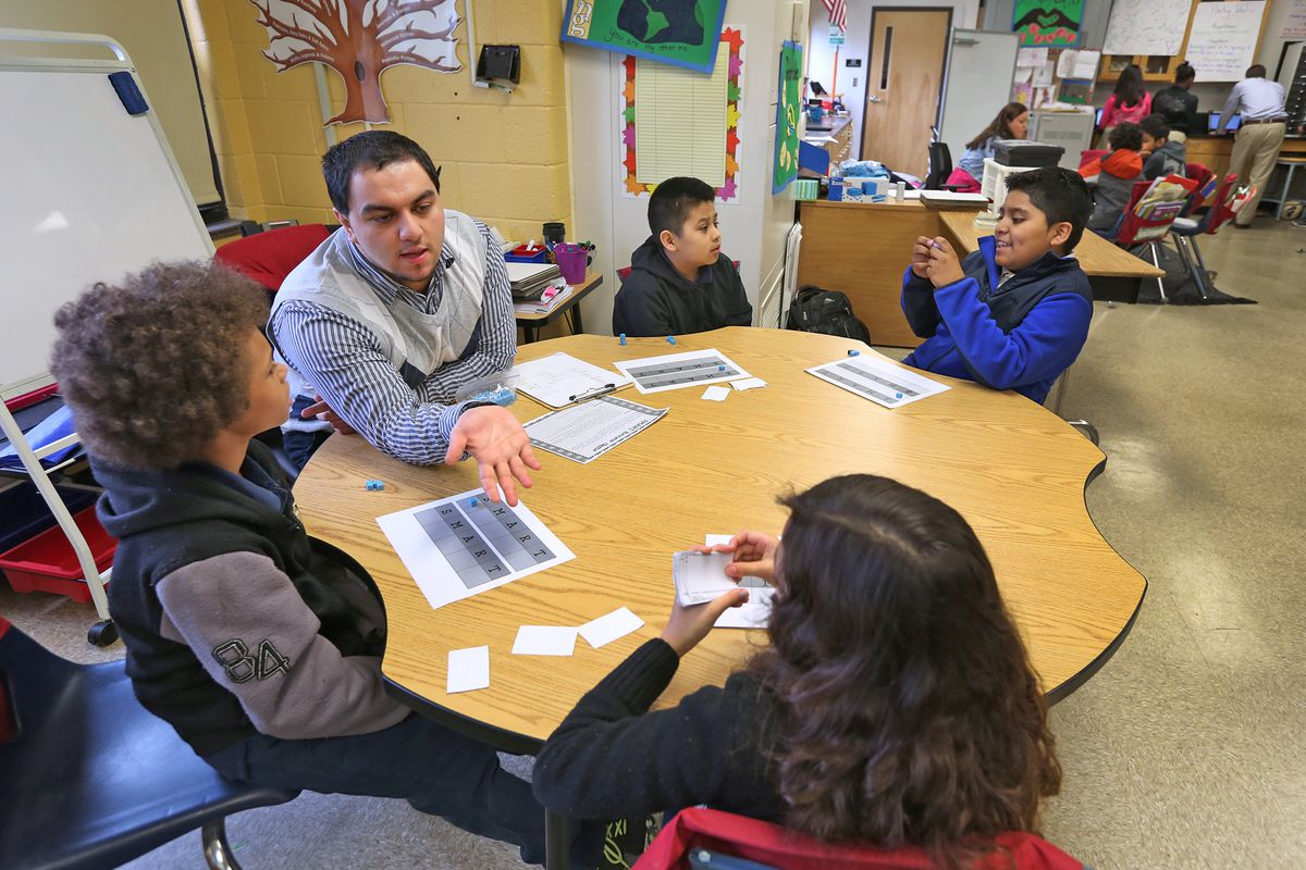 Fourth grade instructional aid Henry Velasquez works with students at Enlace Academy. More than half of the school's students are English learners.