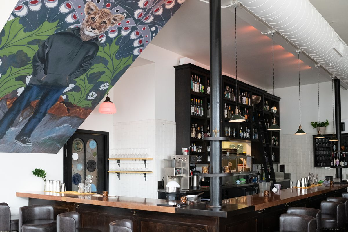 The interior of the restaurant with a side view of the bar. At the front, on the ceiling is a mural of an adolescent with a lion head and human body, in a zip up sweatshirt, jeans, and sneaks. The background is an abstract flower pattern in blue, white, and red.
