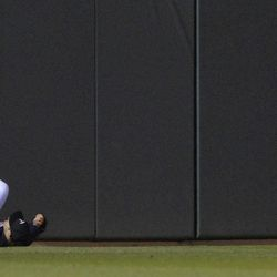 Minnesota Twins left fielder Josh Willingham falls as he tries to field an inside-the-park, three-run home run by Los Angeles Angels' Peter Bourjos in the fifth inning of a baseball game Wednesday, April 11, 2012, in Minneapolis.