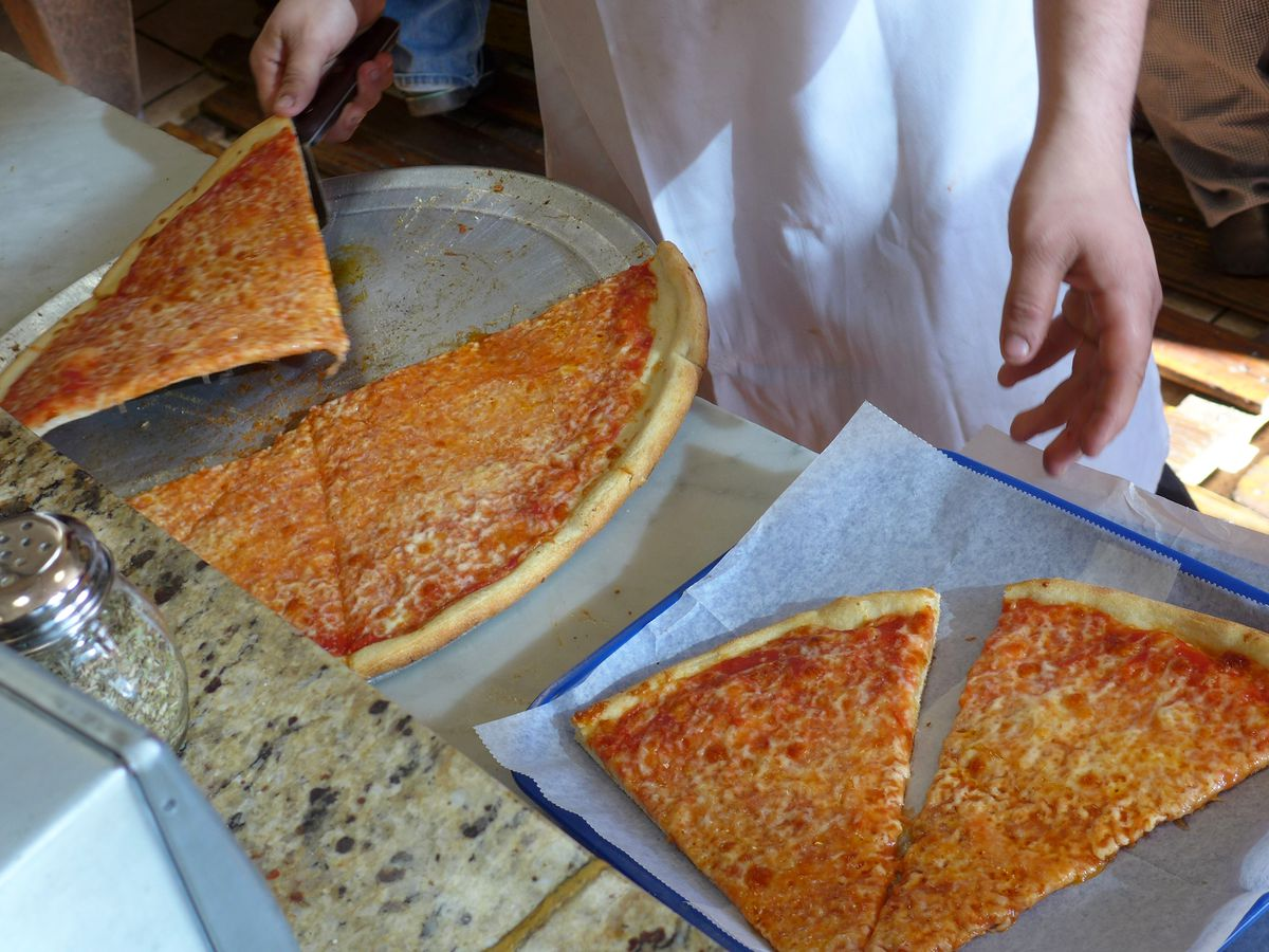 Slices of bright orange pizza being lifted two at a time off a pizza pan and deposited in a cardboard box.
