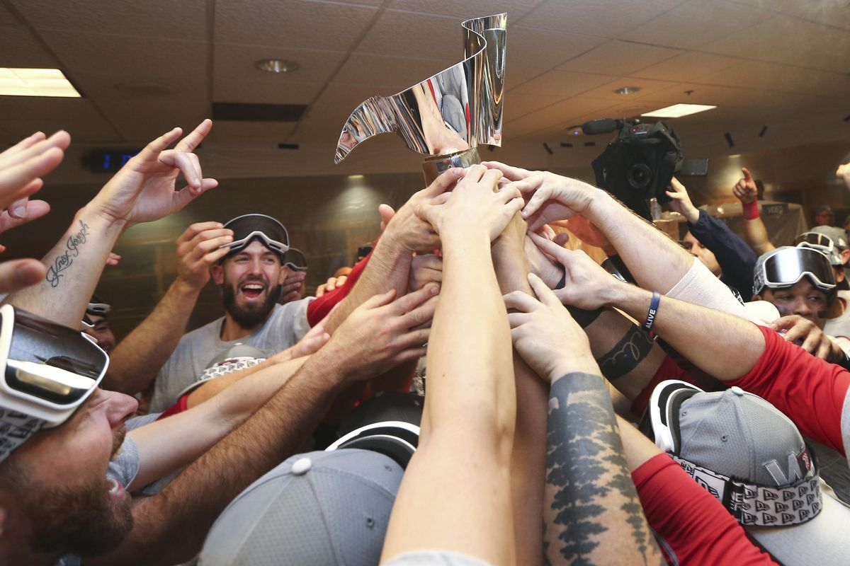 Boston Red Sox players celebrate with the William Harridge Trophy in the clubhouse after defeating the Houston Astros in game five of the 2018 ALCS playoff baseball series at Minute Maid Park.