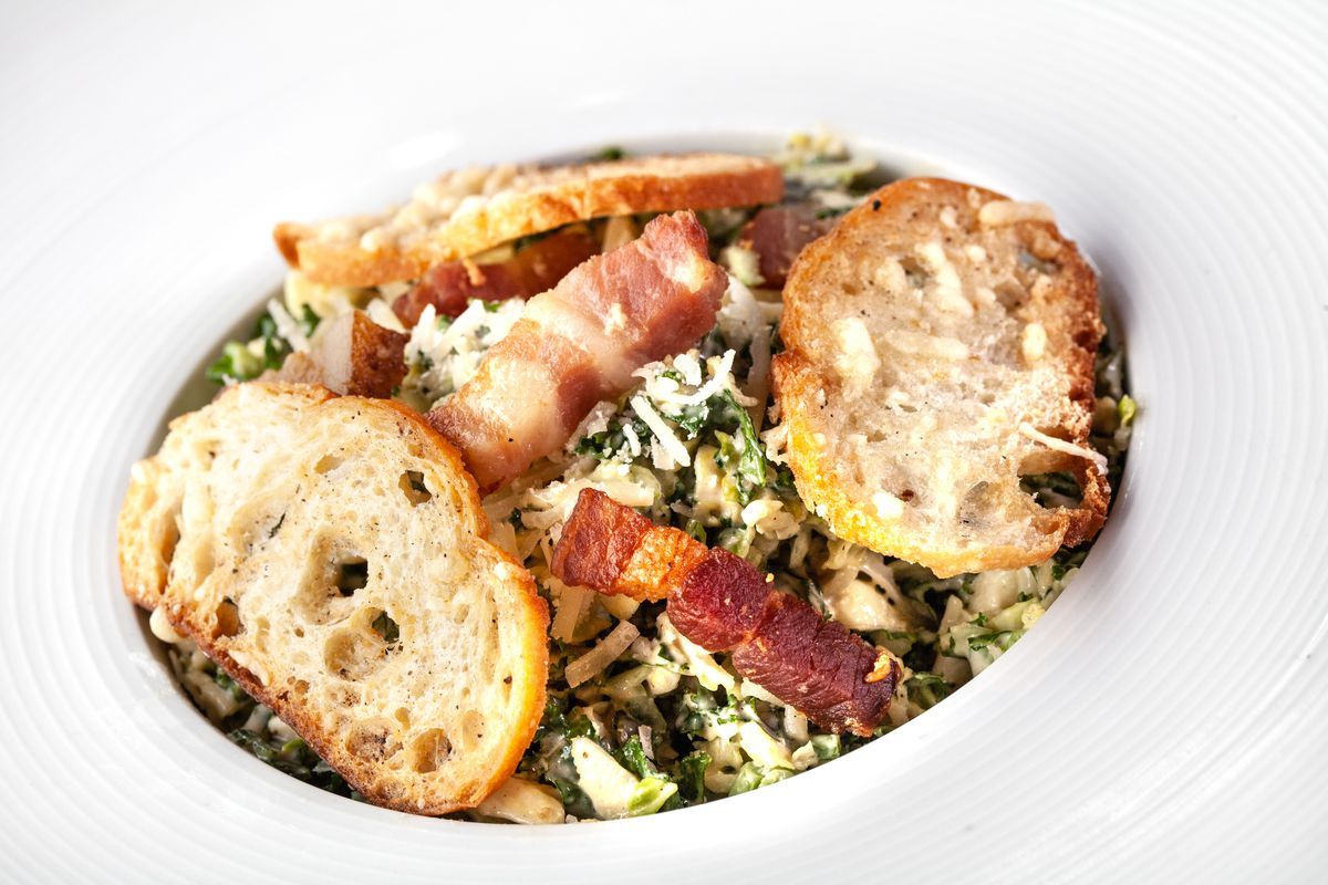a Brussel sprout caesar salad with kale and bacon lardon
