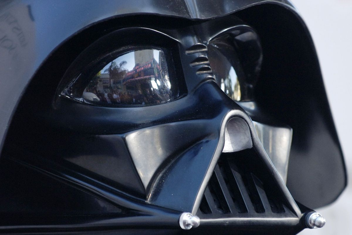 """In this file photo dated Thursday, May 12, 2005, the Los Angeles, USA, premiere of the movie """"Star Wars: Revenge of the Sith"""", is reflected in the mask eyeglasses of iconic baddie character Darth Vader. Disney+ will soon add a number of classic 'Star Wars' shows linked to 'The Star Wars Holiday Special'"""
