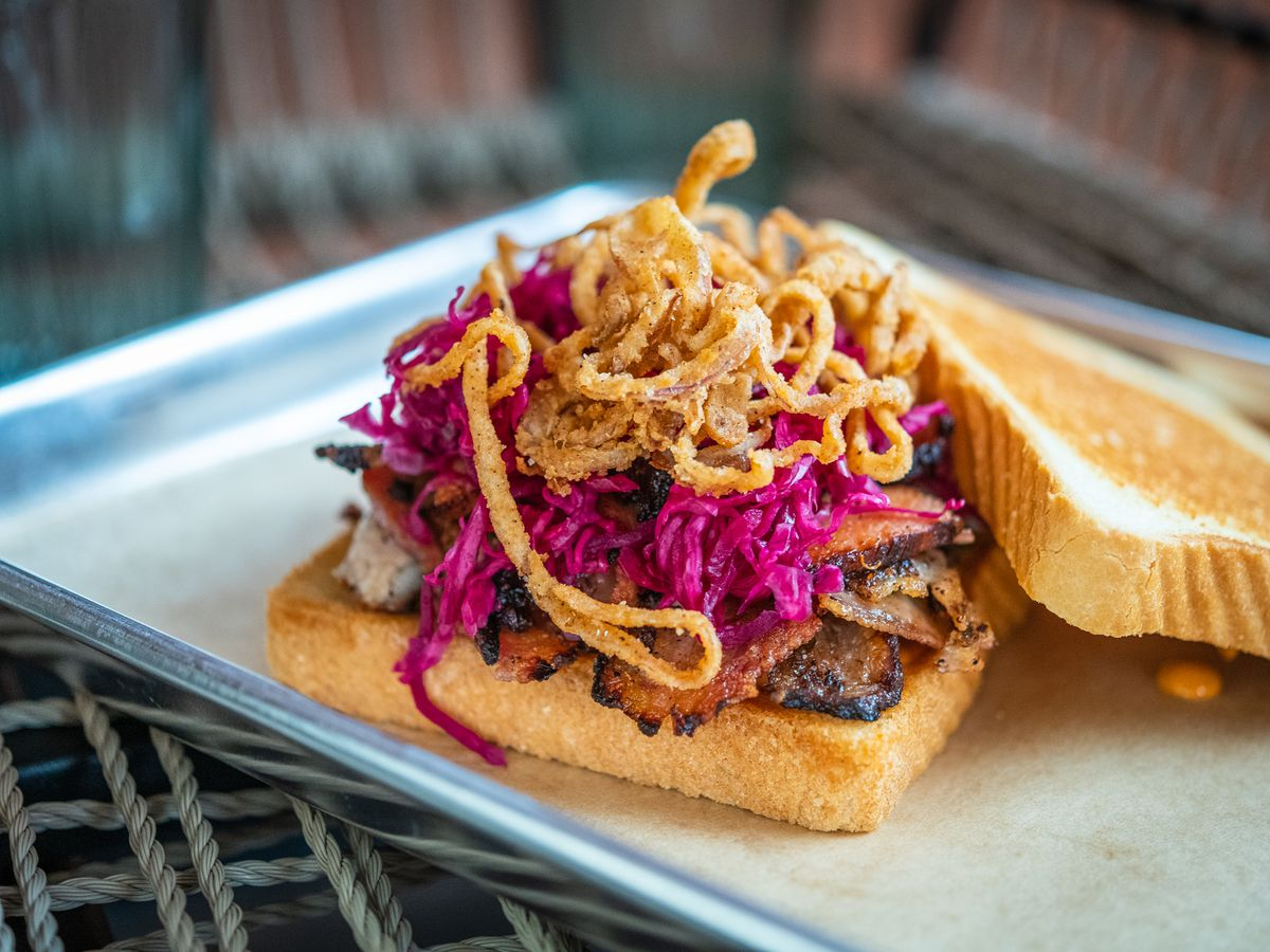 A smoked pork belly pastrami sandwich at Lulu's Winegarden comes on Texas Toast with fermented red cabbage, pickles, lots of crispy shallots, and an aioli made from pork drippings