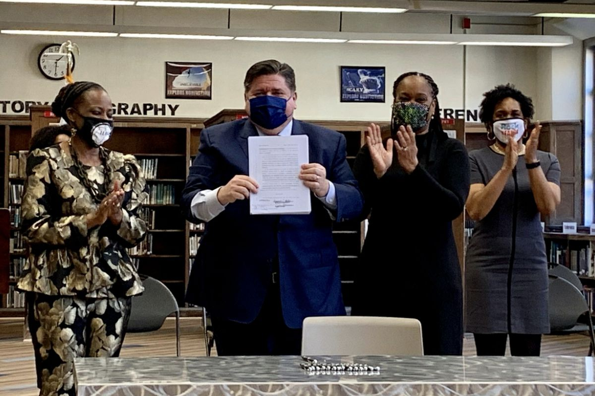 Gov. J.B. Pritzker holds up the signed Education and Workforce Equity Act at Proviso East High School on Monday as, left to right, state Rep. Carol Ammons, state Senate Majority Leader Kimberly Lightford, and Lt. Gov. Juliana Stratton applaud.