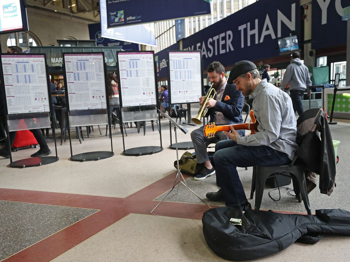 Buskers at a busy train station, one playing a trumpet, the other a guitar.