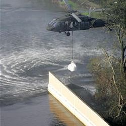 A helicopter drops sandbags Thursday to fill a section of a levee that broke, allowing floodwaters from Hurricane Katrina to fill the streets in New Orleans.