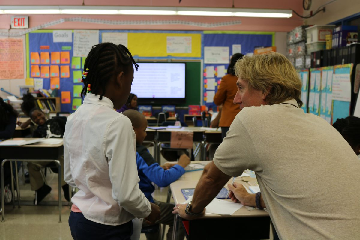 A teacher works at a desk with a young student with braided hair wearing a white dress shirt in the classroom.