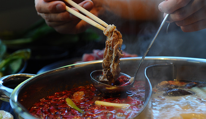 A person dunks meat into hot pot filled with chiles