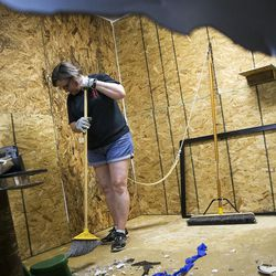 Shawn Baker, the owner of Tantrums, is seen through a destroyed TV cleaning up a destruction room at Tantrums in Houston on Saturday, July 15, 2017. Tantrums is a business where people can let off steam by using bats, poles, golf clubs and sledge hammers to destroy TVs, mirrors, cups, sheets of glass and more. Baker started Tantrums after she was laid off from her job in the oil industry, and she said her business acts as therapy to some and fun for others.