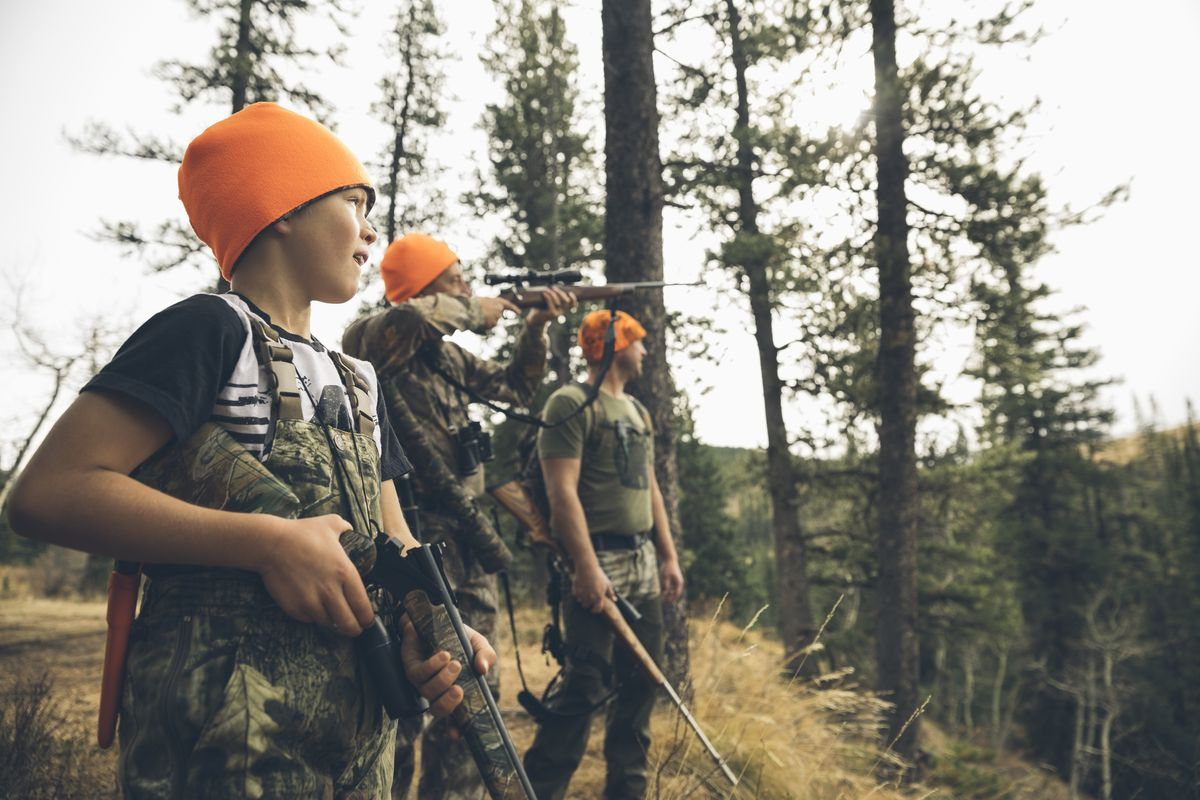 e390b15eee8 An American hunting family in camouflage and orange beanies aim their  hunting rifles on forest ridge. Getty Images Hero Images