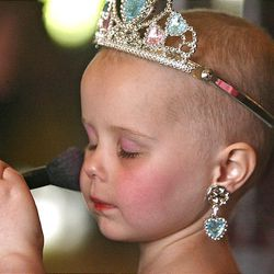 Four-year-old Amelia Flamm closes her eyes while having her makeup applied at the Hope Kids' Princess Party Wednesday at the Castle Reception Center in Layton.