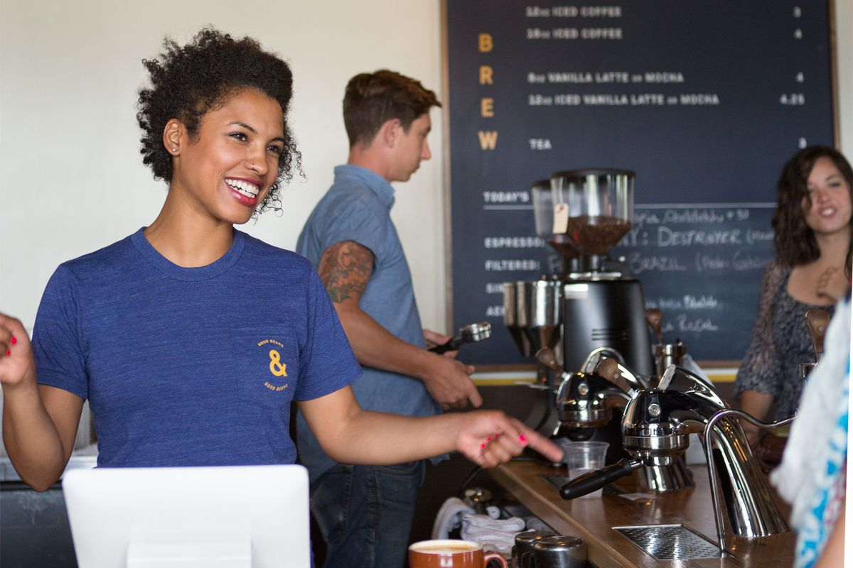A female barista stands behind a counter with coffee machines filling orders using a Square stand.