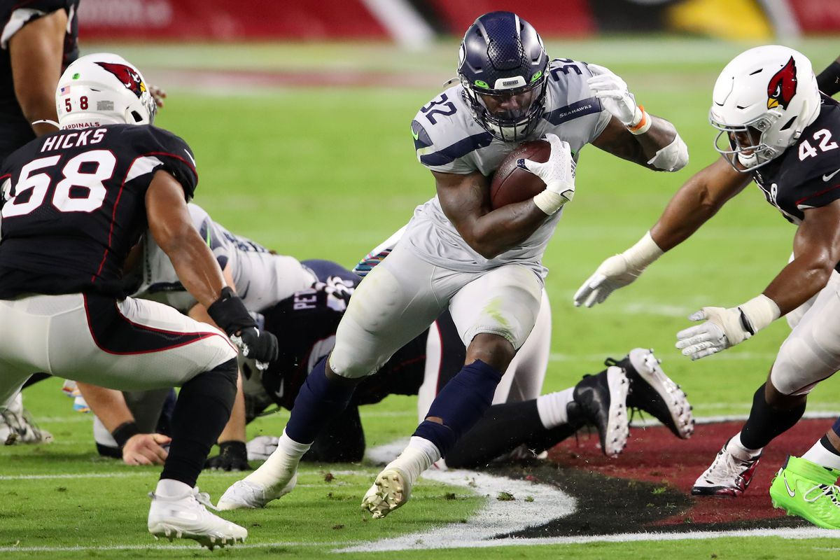 Running back Chris Carson #32 of the Seattle Seahawks runs with the ball against linebacker Jordan Hicks #58 and linebacker Devon Kennard #42 of the Arizona Cardinals in the first quarter of the game at State Farm Stadium on October 25, 2020 in Glendale, Arizona.