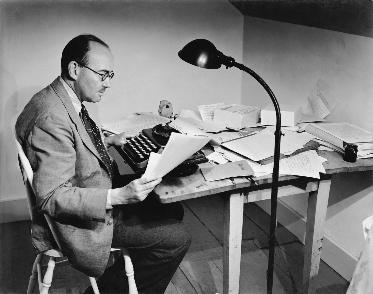 A black and white photo of a man sitting at a small wooden desk with a typewriter in front of him. The desk is covered in a disarray of papers. In the foreground there is a simple floor lamp.