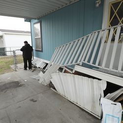 Members of law enforcement survey damage to a mobile home at Western Estates after a 5.7 magnitude earthquake centered in Magna hit on Wednesday, March 18, 2020.