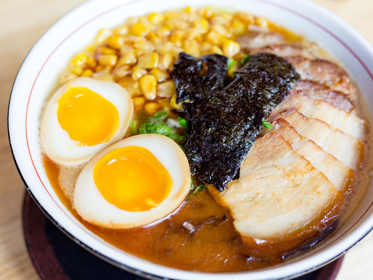 A white bowl filled with brown broth, slices of meat, a halved soft egg, and corn