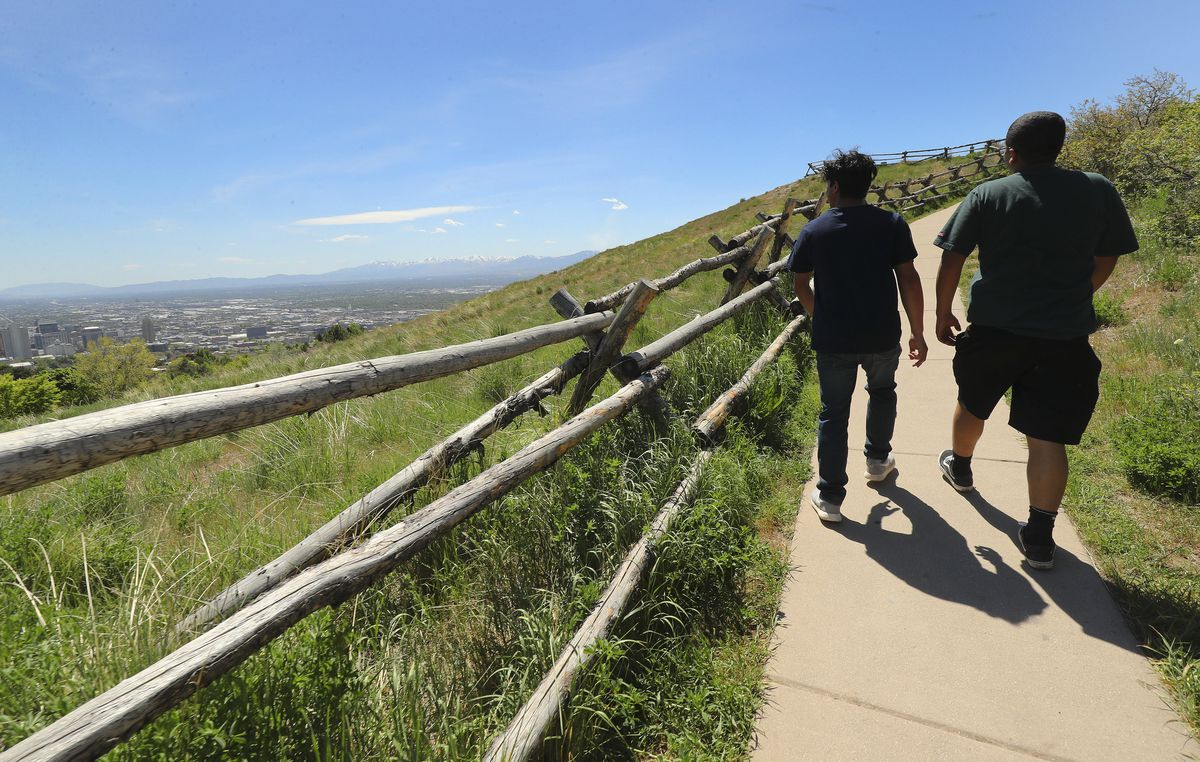Fabio Galvan and Ray Guillen walk on the Ensign Peak Preserve Trail in Salt Lake City on Tuesday, May 5, 2020. A new analysis shows the coronavirus shutdown of schools and businesses dramatically reduced pollutants that form ugly haze and threaten public health.
