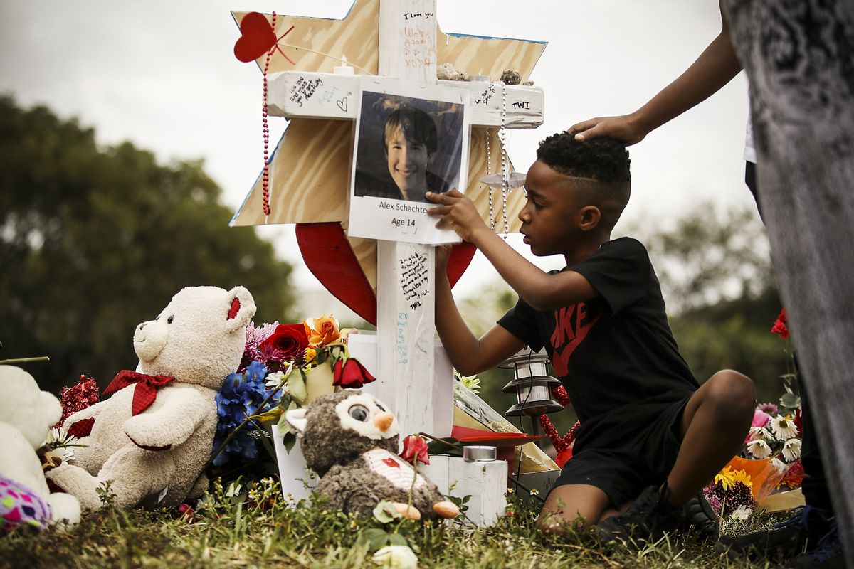 Nekhi Charlemagne writes a message on a cross setup in a makeshift memorial in front of Marjory Stoneman Douglas High School on February 19, 2018 in Parkland, Florida.