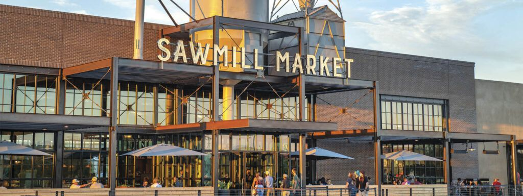 An industrial exterior with patio umbrellas and a few customers visible from afar, and large cutout letters spelling out Sawmill Market