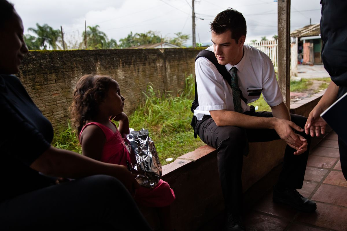 Elders Tanner McKee and Pedro Cabral, right, both missionaries for The Church of Jesus Christ of Latter-day Saints, talk to Liz Cristina and her daughter, Isabella Vitoria, outside their home in Paranaguá, Brazil, on Saturday, June 1, 2019.