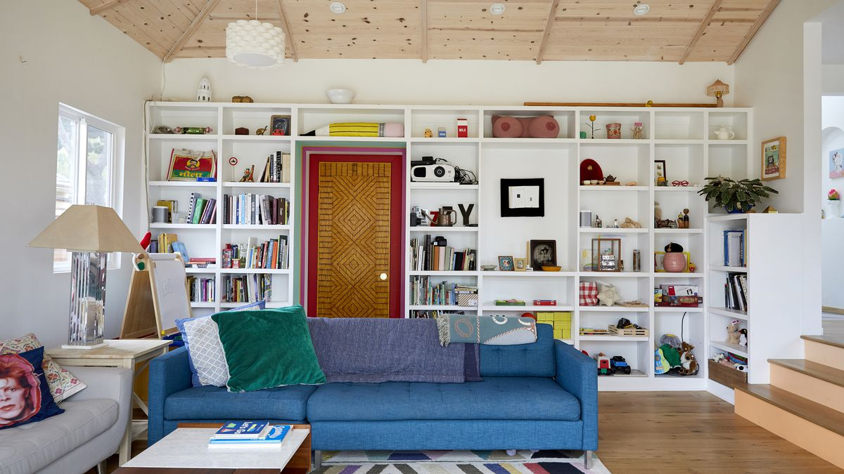 A living room with two couches. One couch is blue, the other couch is grey. On one of the walls are bookshelves full of books, and art. The bookcase surrounds a door with a painted red doorframe.