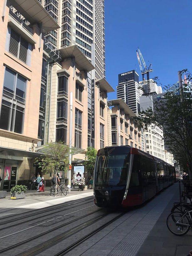 A streetcar show going down a main street in Sydney Australia.