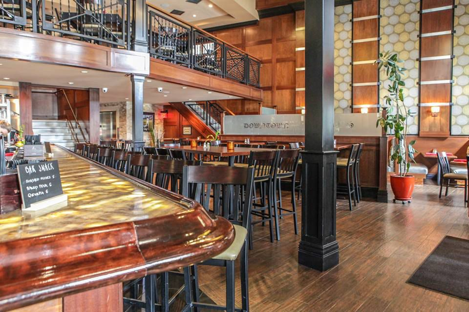 The dining room of Downtown Louie's includes a bar, a communal table, and second-floor seating