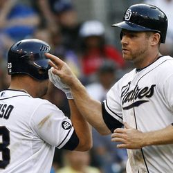 San Diego Padres' Chase Headley high-fives Yonder Alonso (23) after scoring in the seventh inning against the Los Angeles Dodgers in a baseball game, Wednesday, Sept. 26, 2012, in San Diego.