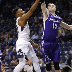 Brigham Young Cougars guard Jahshire Hardnett (0) drive son Portland Pilots center Philipp Hartwich (15)  in Provo on Thursday, Dec. 28, 2017.