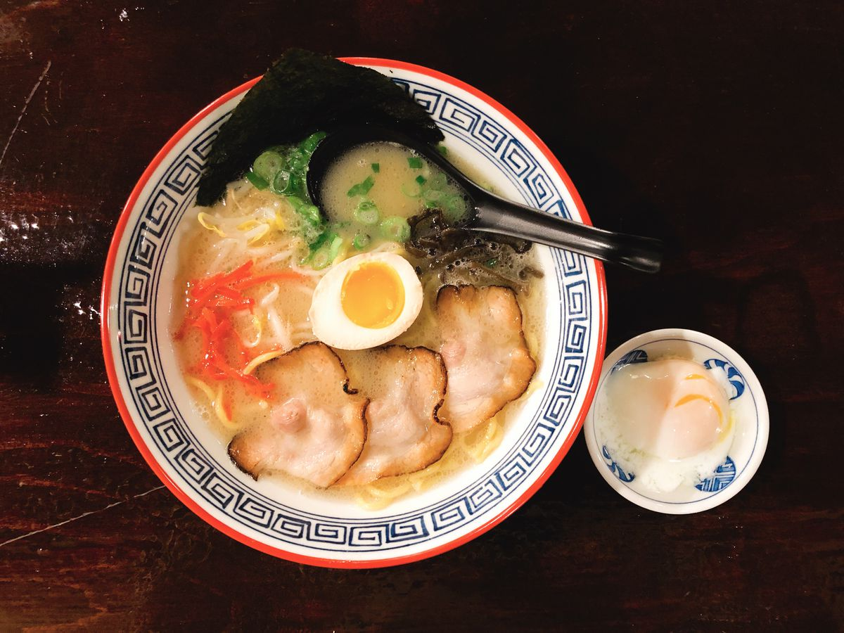 a bowl of ramen with a black spoon, slices of meat, chopped vegetables, and a soft egg