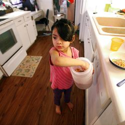 Juliza Carreon, 5, makes a bowl of cereal at home in Taylorsville on Saturday, Feb. 9, 2013. Carreron's family was recently evicted, but they managed to land on their feet.