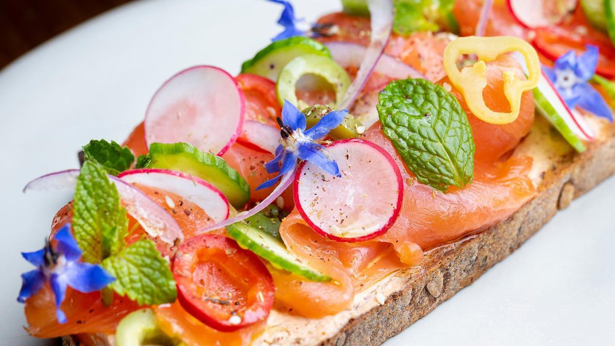 A colorful smoked salmon tartine on a bright white plate.