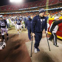 Dejected BYU quarterback Taysom Hill (4) on crutches as he exits Arrowhead Stadium in Kansas City, Missouri, Saturday, Nov. 14, 2015. BYU lost to Missouri, 20-16.
