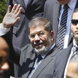 """Egyptian President Mohammed Morsi waves to photographers as he leaves the Arab League headquarters in Cairo, Egypt, Wednesday, Sept. 5, 2012. Morsi says Syrian leader Bashar Assad must learn from """"recent history"""" and step down before it is too late."""