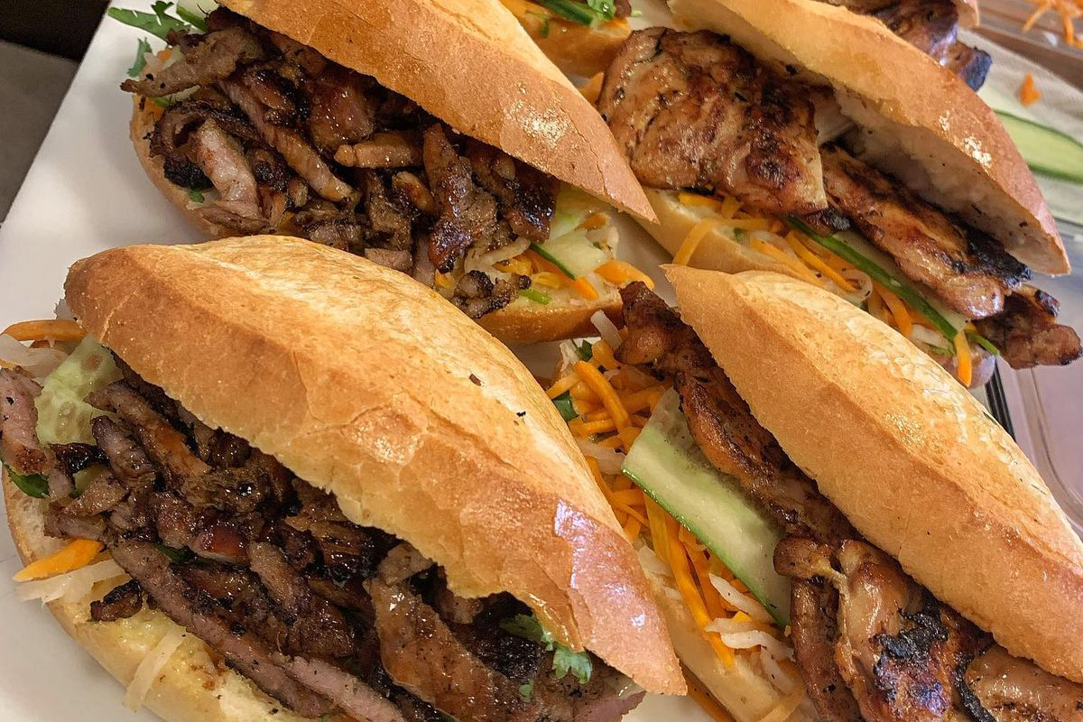 Two rows of banh mi sandwiches with grilled meat and fresh vegetables.