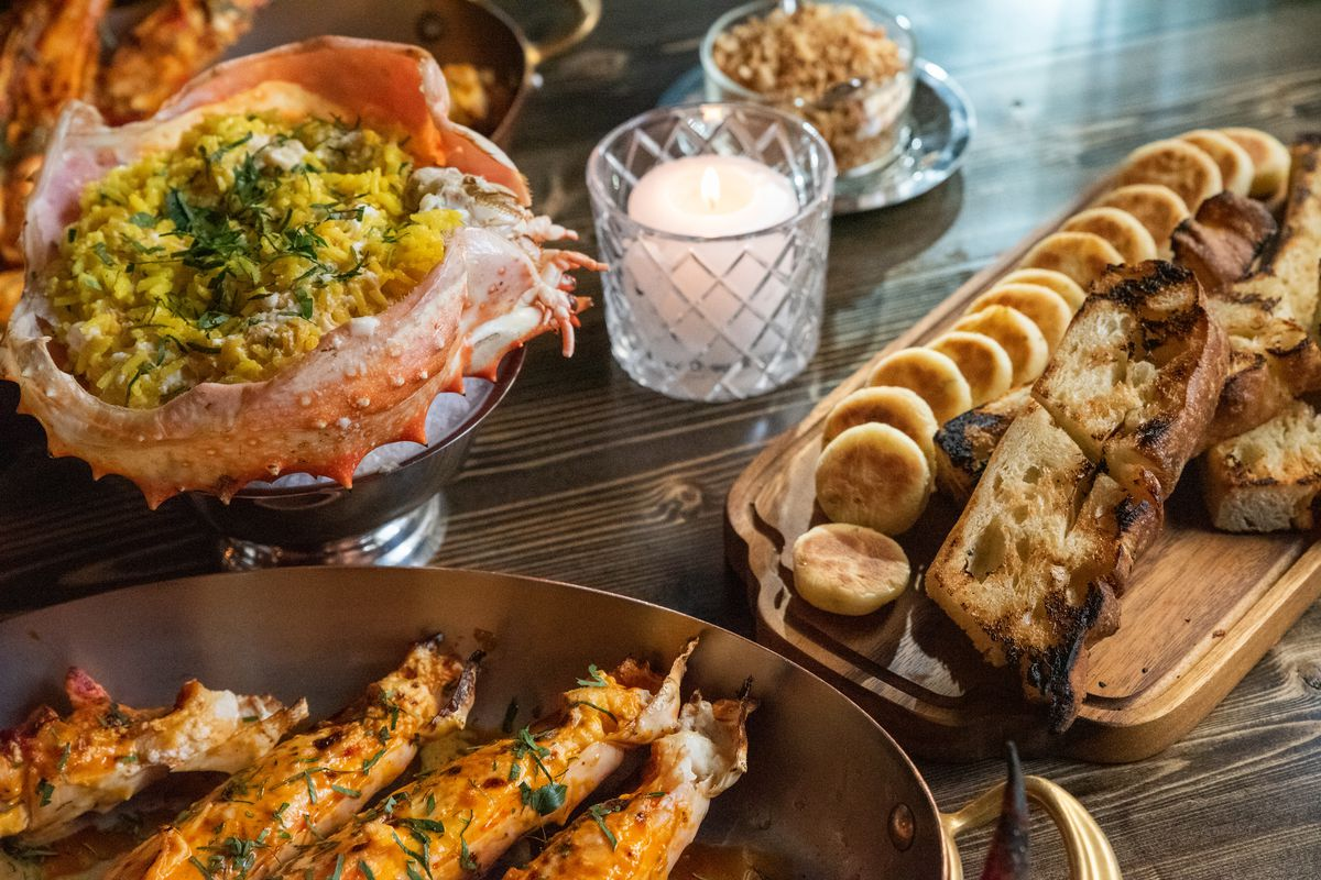 A tabletop with a large shellfish filled with yellow rice, a wood board of bread sits off to the left. In the foreground, fire-roasted crab legs sit in a copper skillet.