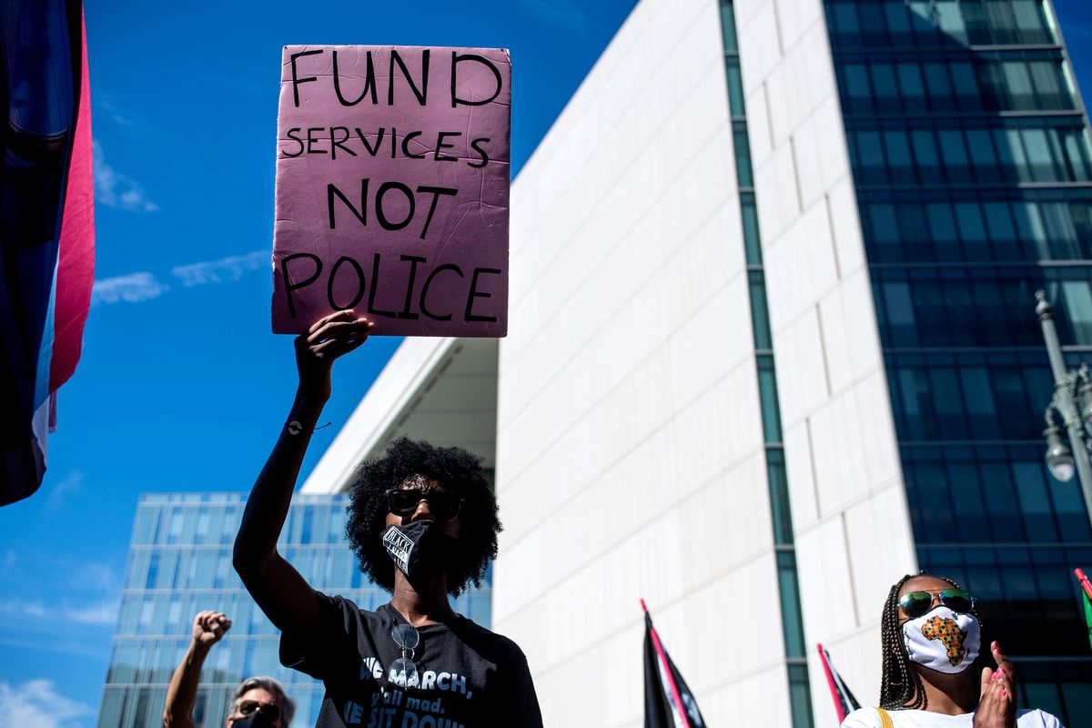 """A protester holds up a sign that reads, """"Fund services, not police."""""""