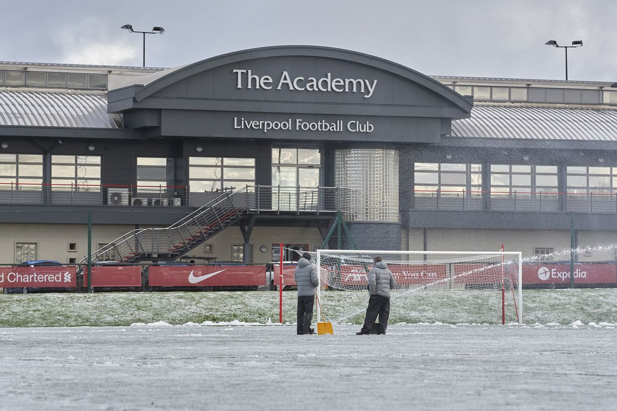 Liverpool ground staff attempting to clear snow from the pitch to enable the PL2 game at AXA Training Centre on January 23, 2021 in Kirkby, England.