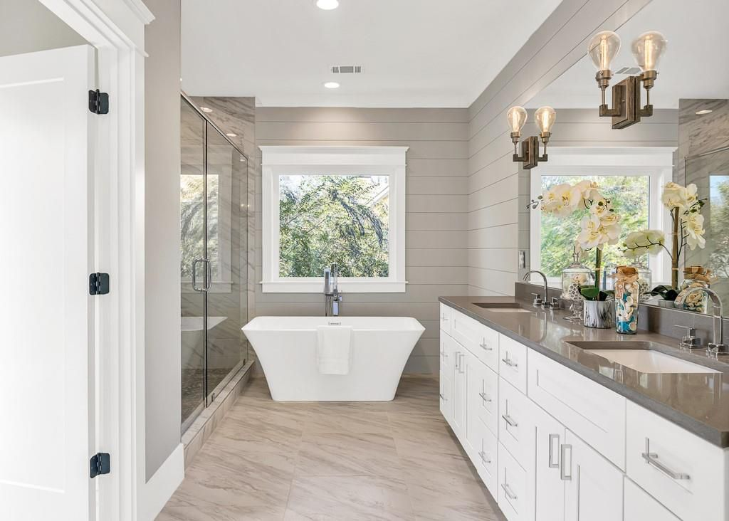 A big master bathroom with stone counters and shiplap on the walls.
