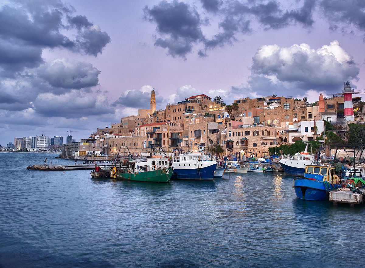The Jaffa port in Tel Aviv. In the foreground is a body of water with boats. In the distance are many buildings.