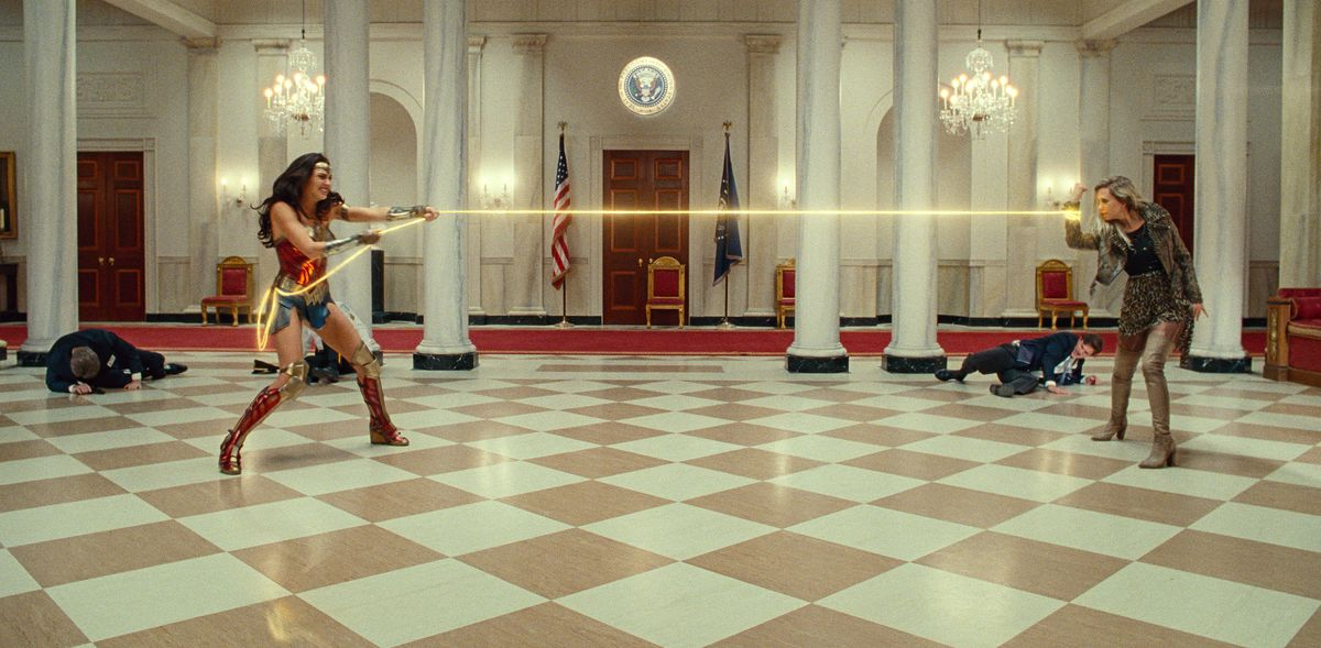 Wonder Woman pulls on her golden lasso, which is wrapped around the arm of Barbara Minerva in Wonder Woman 1984.