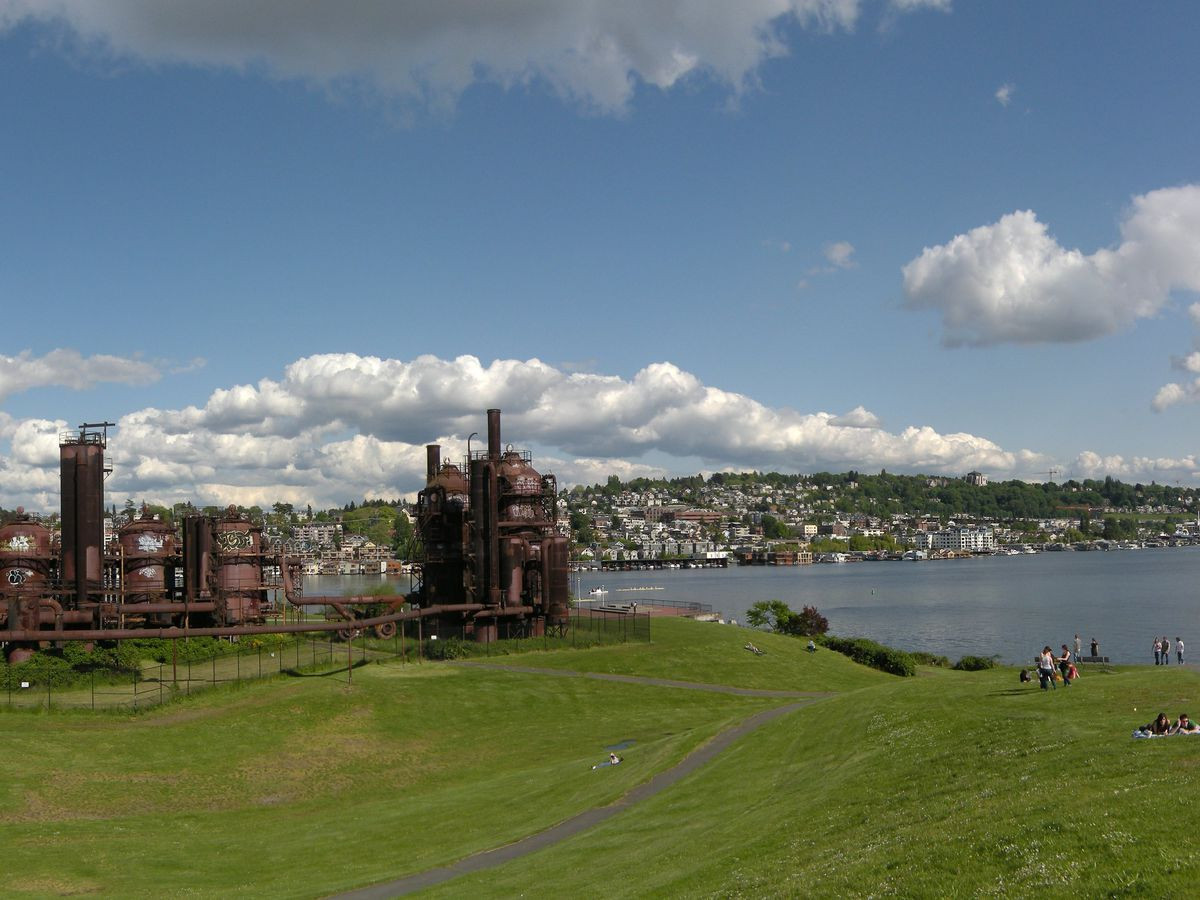 An aerial view of Gas Works Park. There is a large green lawn and at the edge of the lawn is an industrial coal plant.