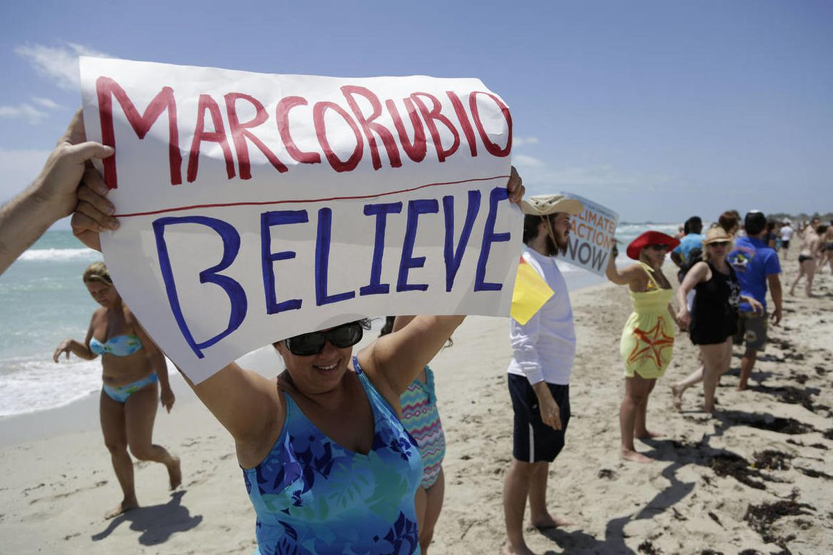 Blanca Mesa of Miami holds a sign protesting Sen. Marco Rubio's statements on climate change as activists and beachgoers join hands while participating in Hands across the Sand, Saturday, May 17, 2014, in Miami Beach, Fla.