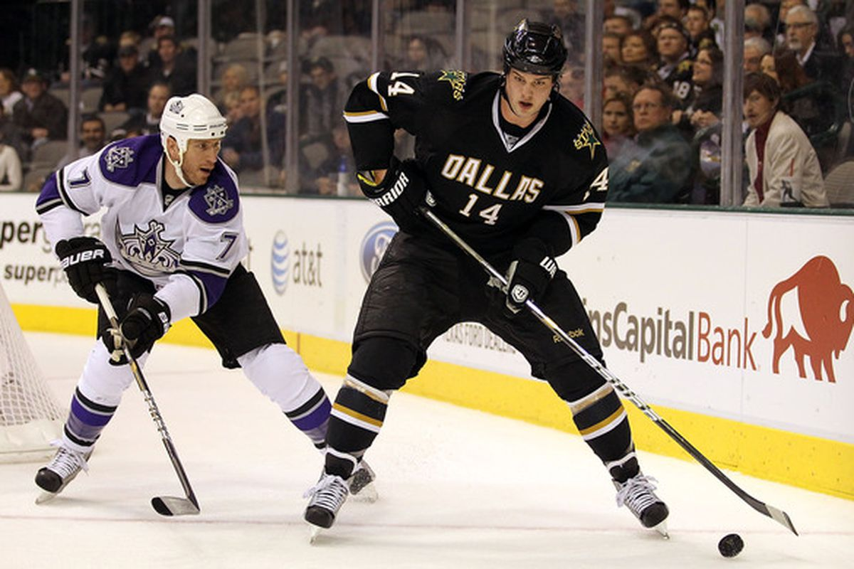 DALLAS TX - JANUARY 17:  Left wing Jamie Benn #14 of the Dallas Stars skates the puck past Rob Scuderi #7 of the Los Angeles Kings at American Airlines Center on January 17 2011 in Dallas Texas.  (Photo by Ronald Martinez/Getty Images)